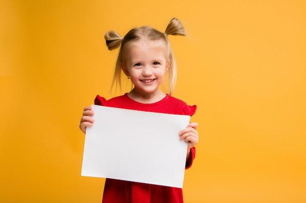 Petite fille tenant une feuille blanche.