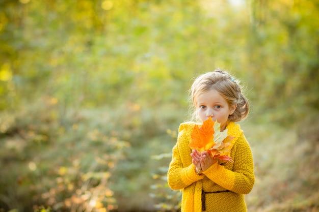 Petite fille tenant des feuilles jaunes.