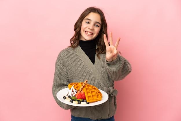 Petite fille tenant des gaufres isolées sur fond rose heureux et en comptant trois avec les doigts