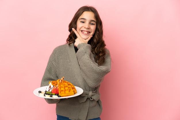 Petite fille tenant des gaufres isolées sur fond rose heureux et souriant