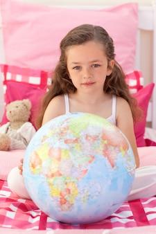 Petite fille tenant un globe terrestre
