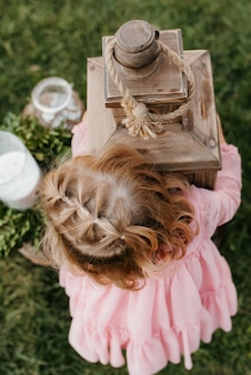 Petite fille tenant une grande lanterne en bois à deux mains