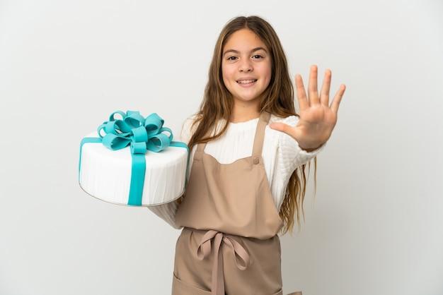 Petite fille tenant un gros gâteau sur fond blanc isolé comptant cinq avec les doigts