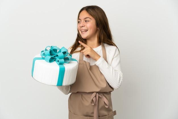 Petite fille tenant un gros gâteau sur fond blanc isolé dans l'intention de réaliser la solution tout en levant un doigt vers le haut