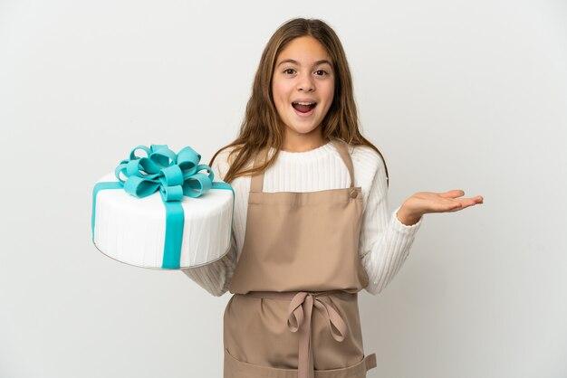 Petite fille tenant un gros gâteau sur fond blanc isolé avec une expression faciale choquée
