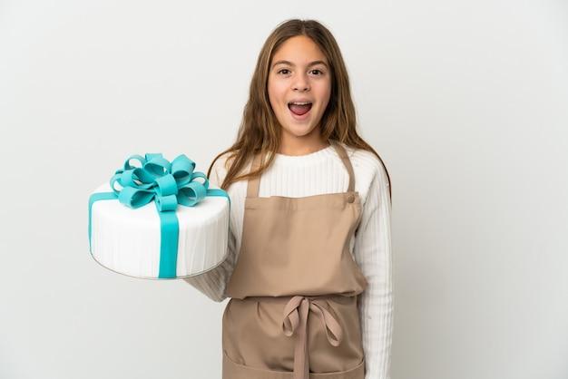 Petite fille tenant un gros gâteau sur fond blanc isolé avec une expression faciale surprise