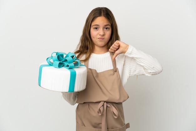 Petite fille tenant un gros gâteau sur fond blanc isolé montrant le pouce vers le bas avec une expression négative