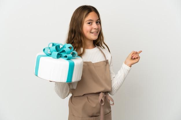 Petite fille tenant un gros gâteau sur fond blanc isolé pointant vers l'arrière