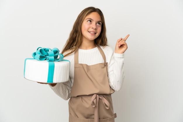 Petite fille tenant un gros gâteau sur fond blanc isolé pointant vers une excellente idée