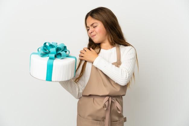 Petite fille tenant un gros gâteau sur fond blanc isolé souffrant de douleurs à l'épaule pour avoir fait un effort