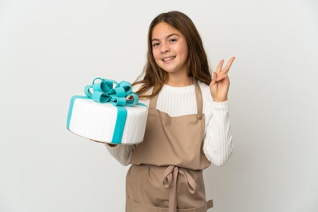 Petite fille tenant un gros gâteau sur fond blanc isolé souriant et montrant le signe de la victoire
