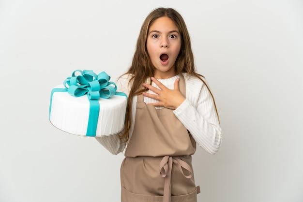 Petite fille tenant un gros gâteau sur fond blanc isolé surpris et choqué en regardant à droite