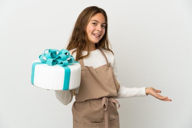 Petite fille tenant un gros gâteau sur fond blanc isolé tendant les mains sur le côté pour inviter à venir