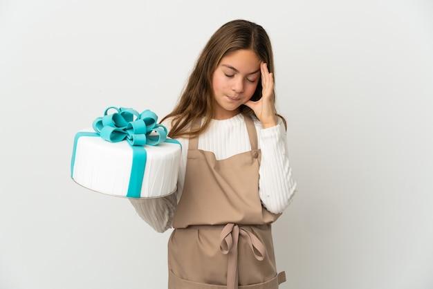 Petite fille tenant un gros gâteau