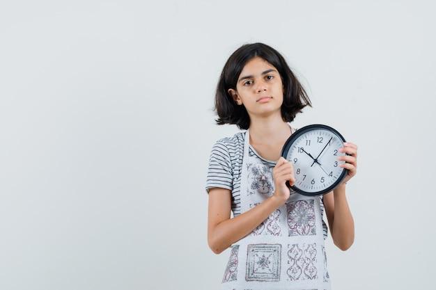 Petite fille tenant une horloge murale en t-shirt, tablier et à la calme,