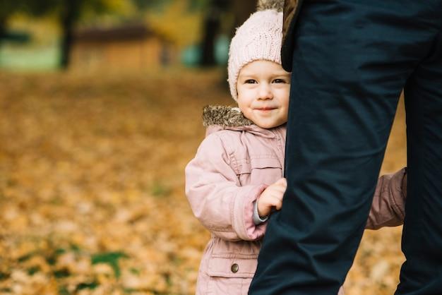 Petite fille tenant sur les jambes de papa en automne parc
