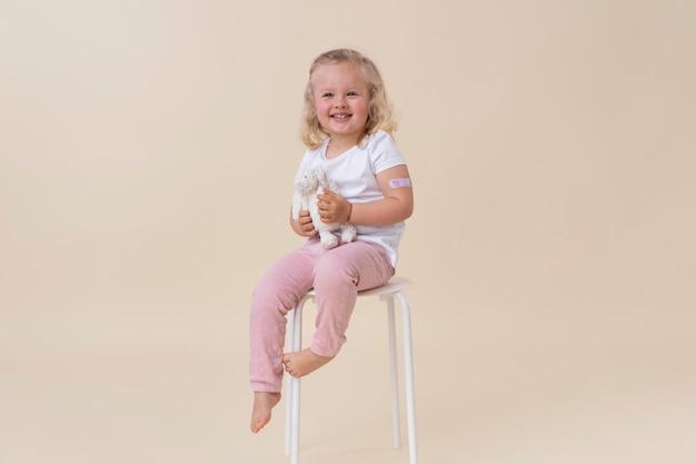 Petite fille tenant un jouet après avoir reçu un vaccin