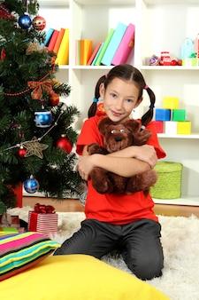 Petite fille tenant un jouet près de l'arbre de noël