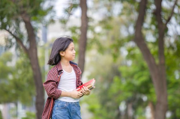 Petite fille tenant un livre et marchant dans le parc