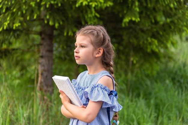 Une petite fille tenant un livre