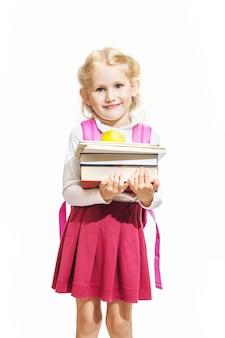 Petite fille tenant des livres et une pomme et faisant isolé sur fond blanc
