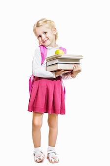 Petite fille tenant des livres et une pomme et isolé sur fond blanc