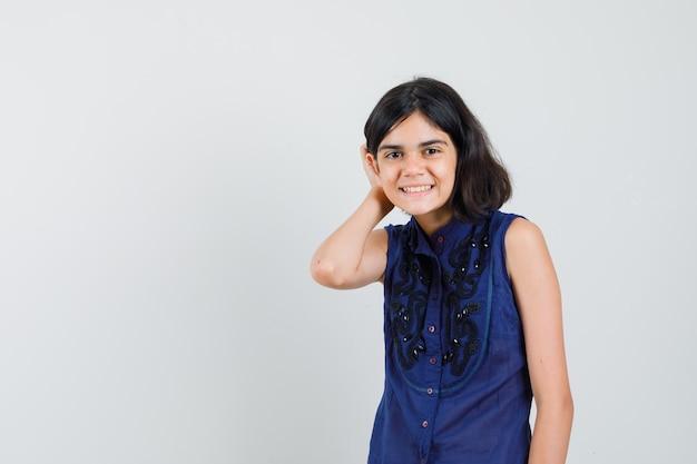 Petite fille tenant la main derrière l'oreille en chemisier bleu et à la joie. vue de face.