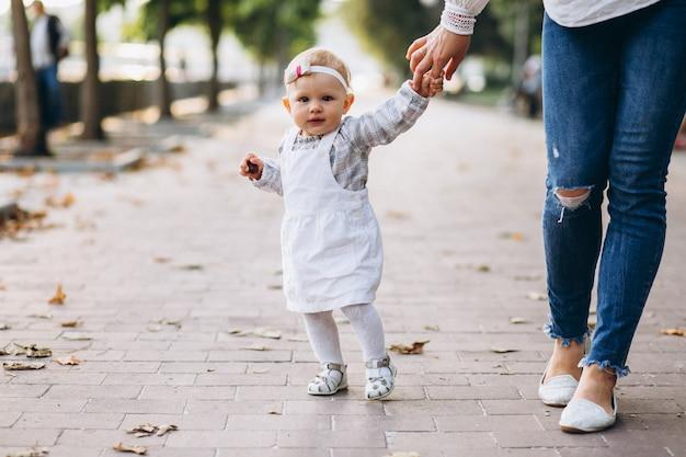 Petite fille tenant la main de la mère dans le parc