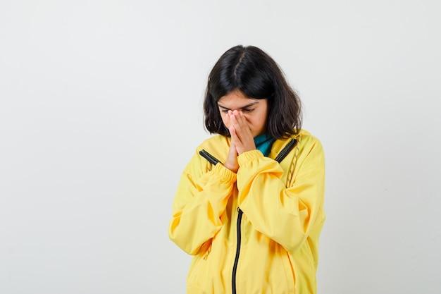 Petite fille tenant la main sur le nez en chemise, veste et à la réflexion. vue de face.