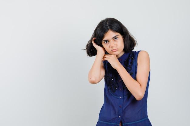 Petite fille tenant la main sur l'oreille en chemisier bleu et à la recherche de sérieux. vue de face.