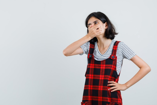Petite fille tenant les mains sur la bouche en t-shirt, combinaison et à la surprise,