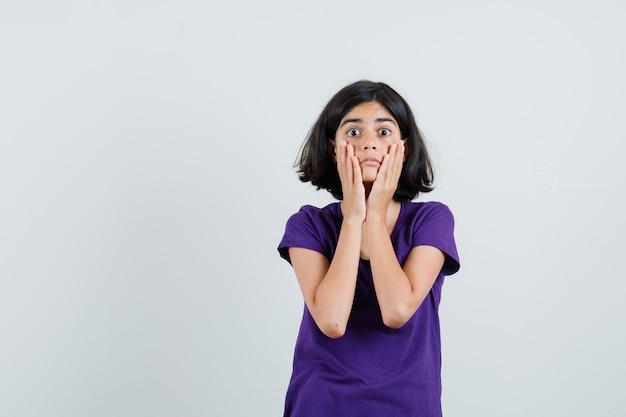 Petite fille tenant les mains sur les joues en t-shirt et à la surprise,
