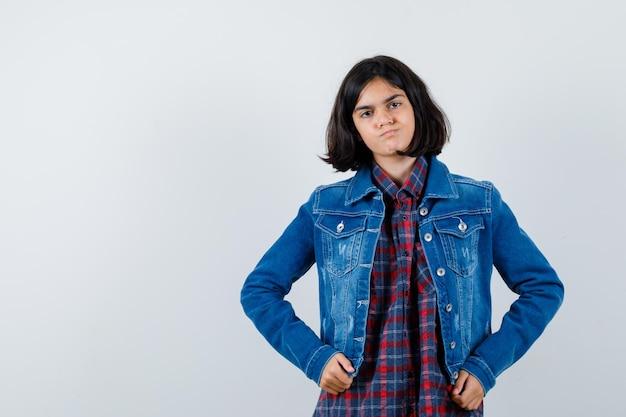 Petite fille tenant les mains sur la taille en chemise, veste et regardant pensive, vue de face.