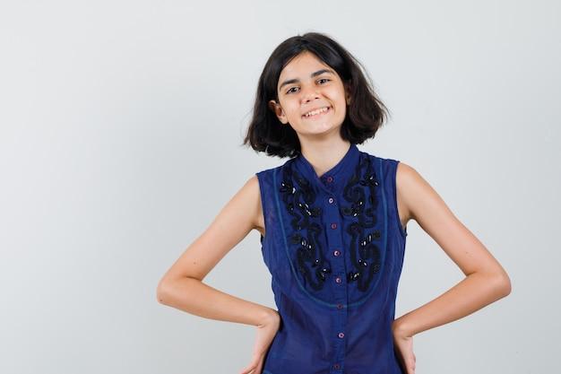 Petite fille tenant les mains sur la taille en chemisier bleu et à la joyeuse. vue de face.