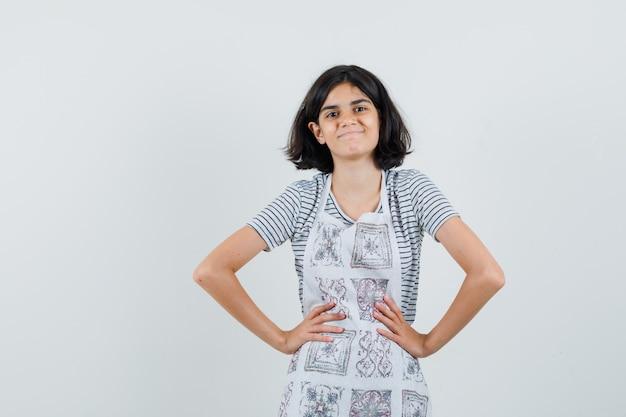 Petite fille tenant les mains sur la taille en t-shirt, tablier et à la joyeuse,