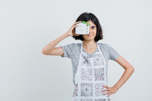 Petite fille tenant le modèle de maison en t-shirt, tablier et à la confiance,