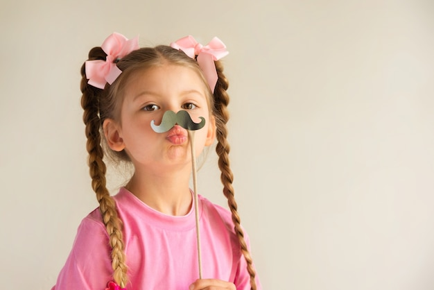 Une petite fille tenant une moustache fantaisie.