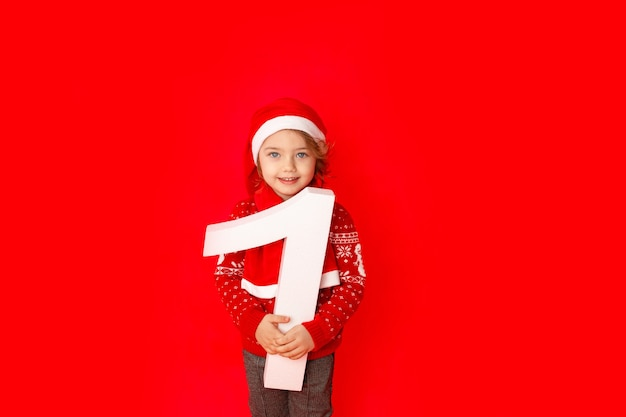 Petite fille tenant le numéro un en bonnet de noel sur fond rouge, espace pour le texte