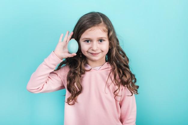 Petite fille tenant un oeuf de pâques bleu