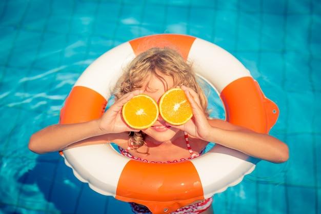 Petite fille tenant des oranges sur ses yeux avec un anneau gonflable dans la piscine