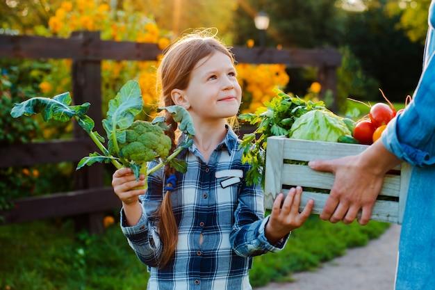 Petite fille tenant un panier de légumes biologiques frais avec sa maman