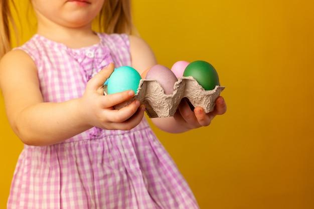 Petite fille tenant le panier avec des oeufs colorés. concept de pâques