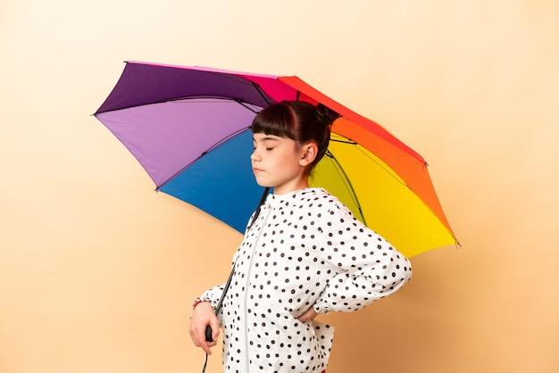 Petite fille tenant un parapluie isolé sur un mur beige souffrant de maux de dos pour avoir fait un effort