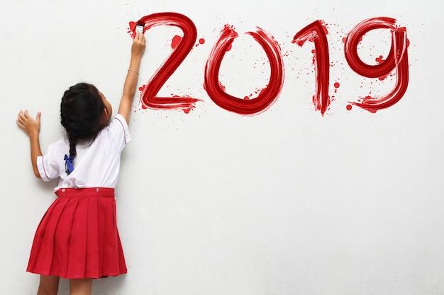 Petite fille tenant une peinture au pinceau bonne année 2019 sur un fond de mur blanc