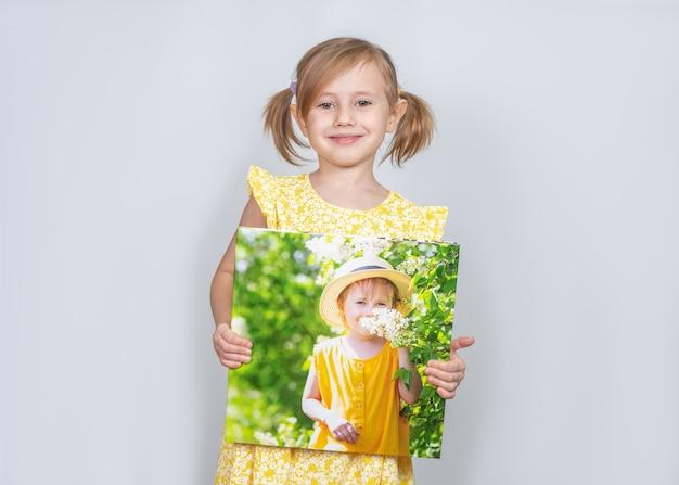Une petite fille tenant un photobook avec ses photographies dans ses mains