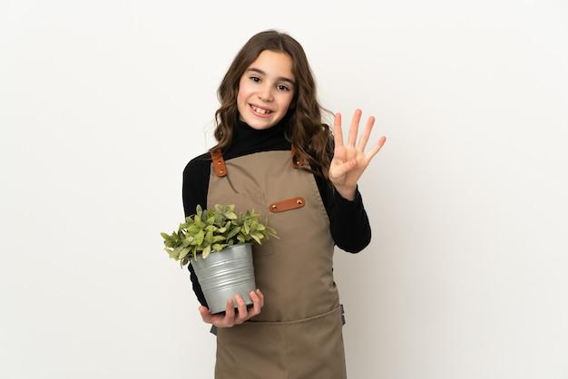 Petite fille tenant une plante isolée sur fond blanc heureux et comptant quatre avec les doigts