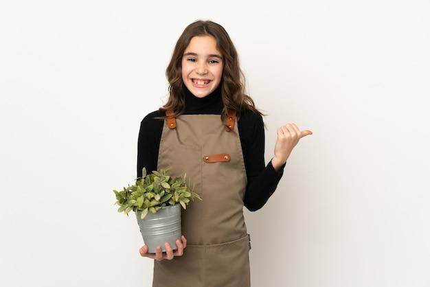 Petite fille tenant une plante isolée sur fond blanc pointant sur le côté pour présenter un produit