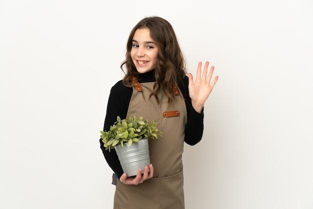Petite fille tenant une plante isolée sur fond blanc saluant avec la main avec une expression heureuse