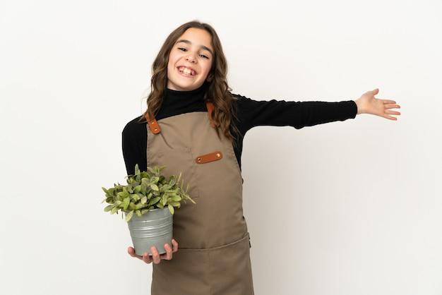 Petite fille tenant une plante isolée sur un mur blanc étendant les mains sur le côté pour inviter à venir