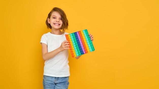 Petite fille tenant pop it jouet antistress sur jaune